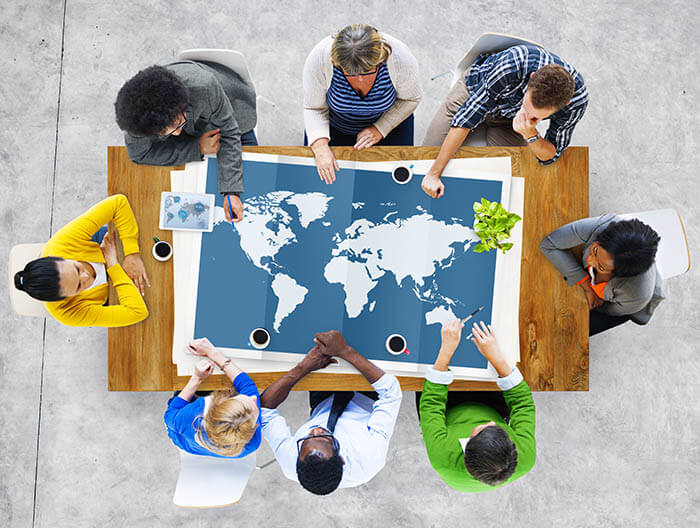 Aerial view of people sitting around a table with a world map on top