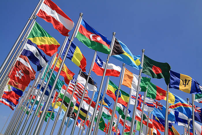 International flags flying against a blue sky